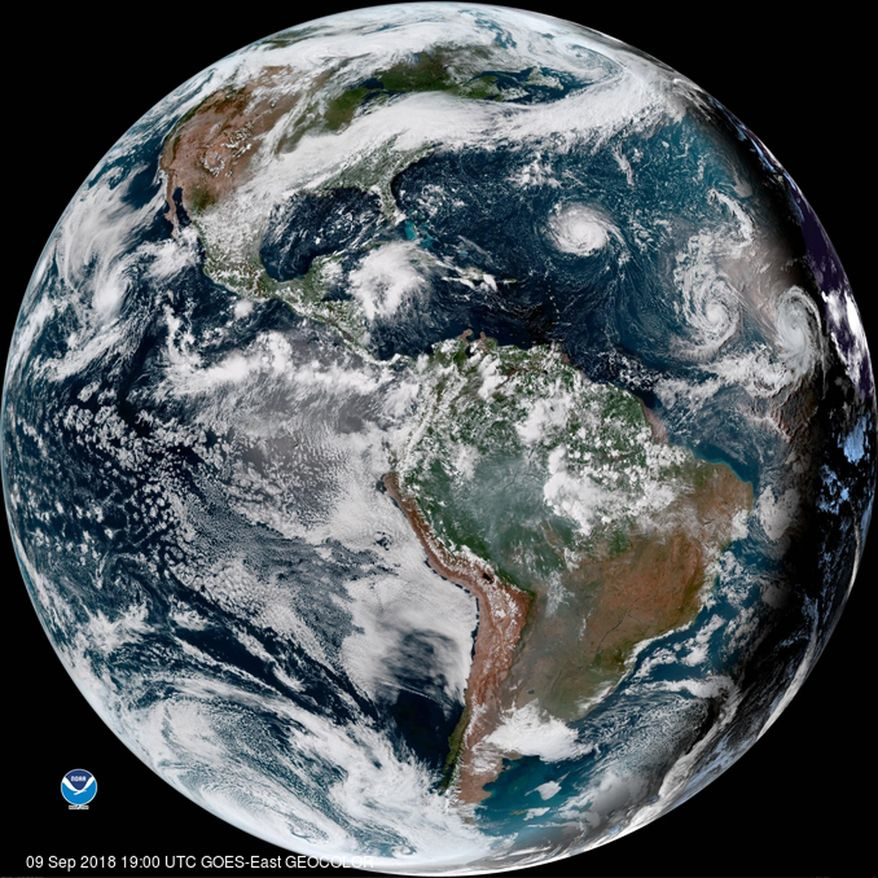 This enhanced satellite image provided by NOAA shows Hurricane Florence, third from right, in the Atlantic Ocean on Sunday, Sept. 9, 2018. At right is Tropical Storm Helene, and second from right is Tropical Storm Isaac. (NOAA via AP)