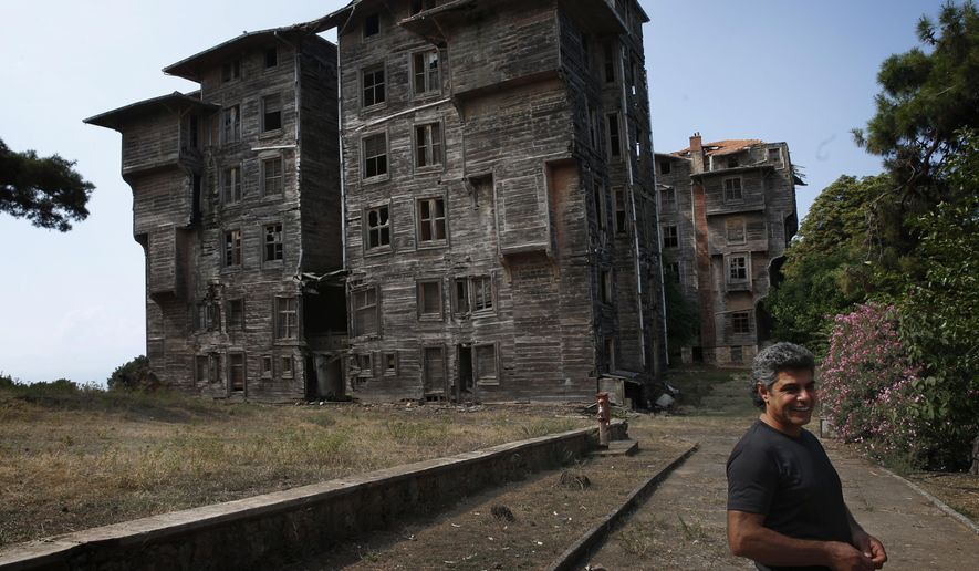 In this Saturday, July 21, 2018 photo, Erol Baytas, 56, the caretaker of the 6-floor timber building that once served as an orphanage for children of the minority Greek community, stands on its grounds, in Buyukada, the largest and most popular of the Princes' Islands in the Sea of Marmara near Istanbul. The 120-year-old gigantic Prinkipo orphanage, occupying 20,000 square meters on a hilltop became home for some 5,800 minority Greek children from 1903 until 1964 when it was forced to shut down. (AP Photo/Lefteris Pitarakis)