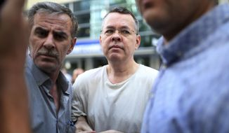 FILE - In this Wednesday, July 25, 2018 file photo, Andrew Craig Brunson, centre, an evangelical pastor from Black Mountain, North Carolina, who had been jailed in Turkey for more than one and a half years on terror and espionage charges, arrives at his house in Izmir, Turkey where he was put under house arrest as his trial continues. Turkey's arrests of Brunson and other Western citizens have thrust its troubled judicial system to the forefront of ties with allies, reinforcing suspicions that the Turkish government is using detainees as diplomatic leverage. (AP Photo/Emre Tazegul, File)