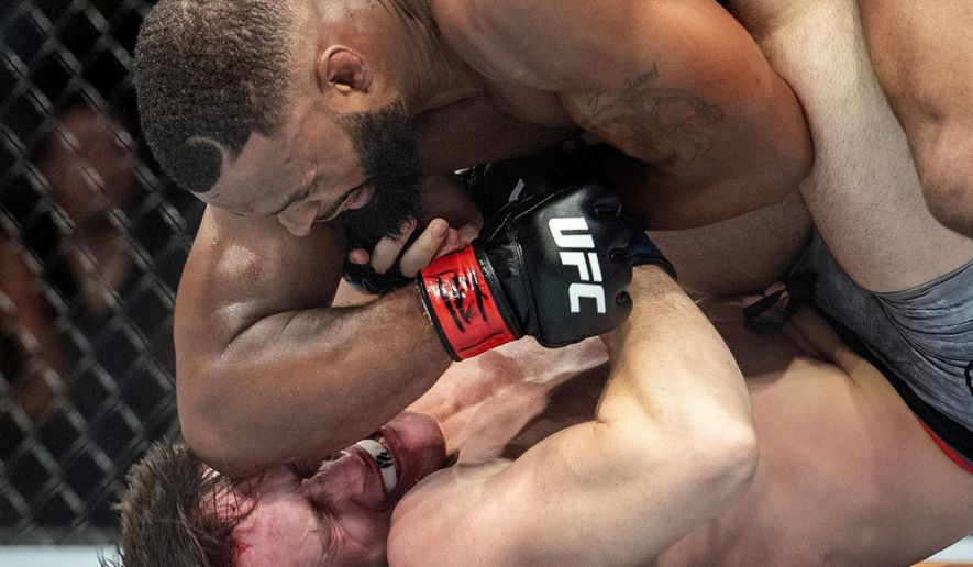 Tyron Woodley, top, elbows Darren Till in the face during their welterweight title mixed martial arts bout at UFC 228 on Saturday, Sept. 8, 2018, in Dallas. Woodley won by submission. (AP Photo/Jeffrey McWhorter)