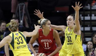Washington Mystics' Elena Delle Donne (11) looks for room to pass as Seattle Storm's Sami Whitcomb (33) and Breanna Stewart (30) defend in the first half of Game 2 of the WNBA basketball finals Sunday, Sept. 9, 2018, in Seattle. (AP Photo/Elaine Thompson)