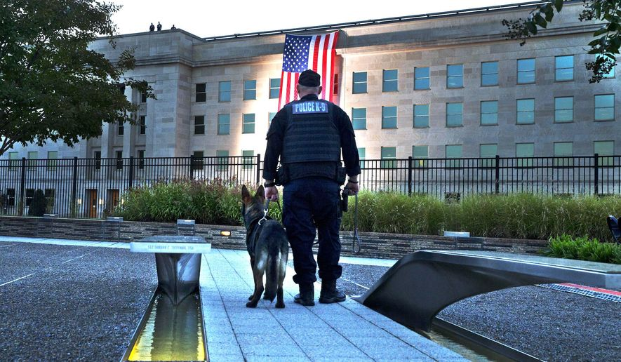 A K-9 officer pauses just prior to a 9/11 memorial event in 2015, as the flag is draped on the Pentagon marking where it was attacked. (Associated Press)