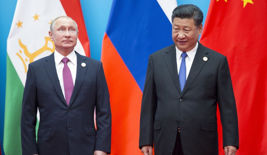 Chinese President Xi Jinping (right) and Russian President Vladimir Putin pose for a photo at the Shanghai Cooperation Organization (SCO) Summit in Qingdao in eastern China's Shandong Province. (AP Photo/Alexander Zemlianichenko, File)