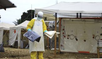 In this photo taken Sunday, Sept 9, 2018, a health worker in protective gear works at an Ebola treatment centre in Beni, Eastern Congo. The current Ebola outbreak in northeastern Congo has become a testing ground with one aid group for the first time treating confirmed Ebola victims in individual biosecure units used in emergencies involving highly infectious diseases. (AP Photo/Al-hadji Kudra Maliro) ** FILE **