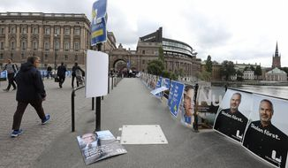 People walk past election posters near the Swedish parliament in Stockholm, Monday Sept. 10, 2018, the day after general elections in Sweden. Sweden was looking at weeks of uncertainty and complex coalition talks after the country's two rival blocs failed to secure a clear governing majority in elections that saw a boost for a far-right party  considered political pariahs  amid growing discontent with large-scale immigration. (Soren Andersson/TT via AP)