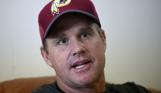 Washington Redskins head coach Jay Gruden speaks as he is interviewed by the Associated Press after an NFL football team practice, Wednesday, June 13, 2018, in Ashburn, Va. The Gruden brothers are set to do something only one other family has done in NFL history. With Jon Gruden leaving the TV booth to return to the sideline for a second stint as coach of the Oakland Raiders and Jay Gruden entering his fifth year with the Washington Redskins, the Grudens will join the Harbaughs as the only sets of siblings to simultaneously hold jobs as NFL head coaches.  (AP Photo/Nick Wass)