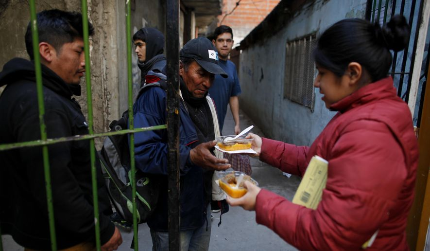 Argentines line up for a small meal outside a soup kitchen at a community center in a shantytown on the outskirts of Buenos Aires. Analysts say that poverty, which affects about a third of the population, will rise this year, and the economy will take a dive. (Associated Press/File)