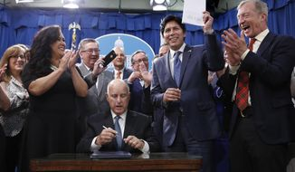State Sen. Kevin de Leon, D-Los Angeles, second from right, displays his environmental measure SB100 after is was signed into law by Calif., Gov. Jerry Brown front center, Monday, Sept. 10, 2018, in Sacramento, Calif. Brown, surrounded by lawmakers and activists including Assembly members Lorena Gonzalez Fletcher, of San Diego, second from left, Ken Cooley, of Rancho Cordova, third from left and billionaire activist Tom Steyer, right, signed SB100 which sets a goal of phasing out all fossil fuels from the state's electricity sector by 2045. (AP Photo/Rich Pedroncelli)