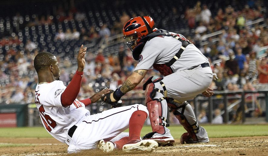 Washington Nationals' Victor Robles, left, slides home to score against St. Louis Cardinals catcher Yadier Molina, right, during the fifth inning of a baseball game on a double by Adam Eaton, Wednesday, Sept. 5, 2018, in Washington. (AP Photo/Nick Wass)