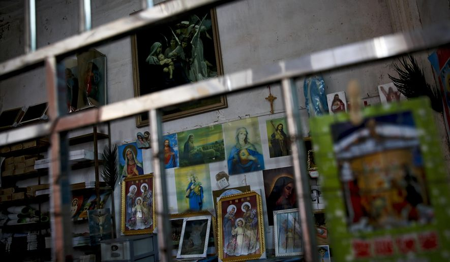 In this Tuesday, March 27, 2018, photo, Catholic religious paintings and Bibles are displayed behind bars at an underground Catholic church in Jiexi county in south China's Guangdong province. A group that monitors Christianity in China says the government is ratcheting up a crackdown on congregations in Beijing and several Chinese provinces, destroying crosses, burning Bibles and ordering followers to sign papers renouncing their faith. (AP Photo/Andy Wong)