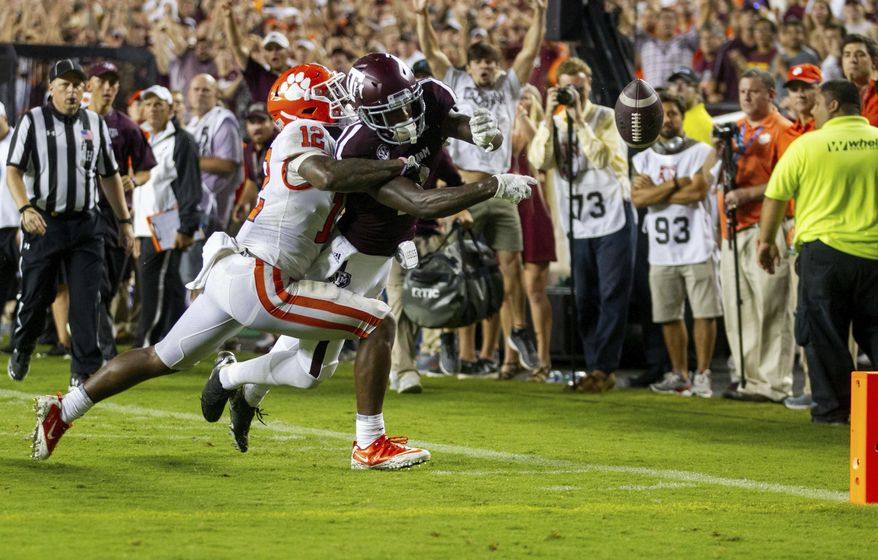 Texas A&M wide receiver Quartney Davis (1) has the ball punched out of his hands for a touchback by Clemson defensive back K'Von Wallace (12) during the fourth quarter of an NCAA college football game Saturday, Sept. 8, 2018, in College Station, Texas. (AP Photo/Sam Craft)