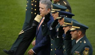 """FILE - In this Aug. 14, 2018 file photo, Colombia's President Ivan Duque reviews the troops, accompanied by his military staff during a ceremony in Bogota, Colombia. The rebel National Liberation Army said Monday, Sept. 10, that it was willing to """"liberate"""" a group of policemen and civilians it captured in August. But the rebels also accused President Ivan Duque of breaking promises made by his predecessor and said they will not accept his """"unilateral"""" conditions. (AP Photo/Fernando Vergara, File)"""
