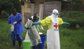 In this photo taken Sunday, Sept 9, 2018, a health worker sprays disinfectant on his colleague after working at an Ebola treatment centre in Beni, Eastern Congo. The current Ebola outbreak in northeastern Congo has become a testing ground with one aid group for the first time treating confirmed Ebola victims in individual biosecure units used in emergencies involving highly infectious diseases. (AP Photo/Al-hadji Kudra Maliro) **FILE**