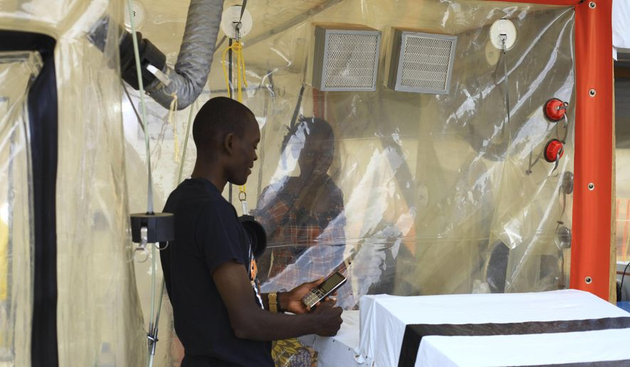 In this photo taken Sunday, Sept 9, 2018, Kasereka Mulanda, 24, is seen talking with his wife who is suffering from the Ebola virus in an isolation area in Beni, Eastern Congo. The current Ebola outbreak in northeastern Congo has become a testing ground with one aid group for the first time treating confirmed Ebola victims in individual biosecure units used in emergencies involving highly infectious diseases. (AP Photo/Al-hadji Kudra Maliro)