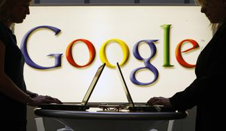 In this April 17, 2007, file photo exhibitors of the Google company work in front of a illuminated sign at the industrial fair Hannover Messe in Hannover, Germany. (AP Photo/Jens Meyer, File)