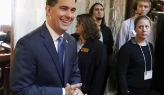FILE - In this Jan. 24, 2018, file photo, Wisconsin Gov. Scott Walker arrives to deliver his state of the state address at the Capitol in Madison, Wis. Walker and his allies are trying to change the conversation of his re-election campaign, as bad news continues to pile up for the two-term Republican incumbent. (Steve Apps/Wisconsin State Journal via AP, File)