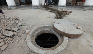 FILE- Sept. 10, 2010 file photo, a laborer works near an open manhole at Connaught Place in the heart of New Delhi, India. Five men have died from exposure to toxic fumes while cleaning a septic tank at a housing complex in New Delhi. Bezwada Wilson of the Sanitation Workers Movement group says more than 1,800 people across India have died while cleaning septic tanks since 2014, when India's Supreme Court issued a ruling to bolster a 2013 act that prohibits employing people to clean sewage without safety equipment. (AP Photo/Saurabh Das, File)