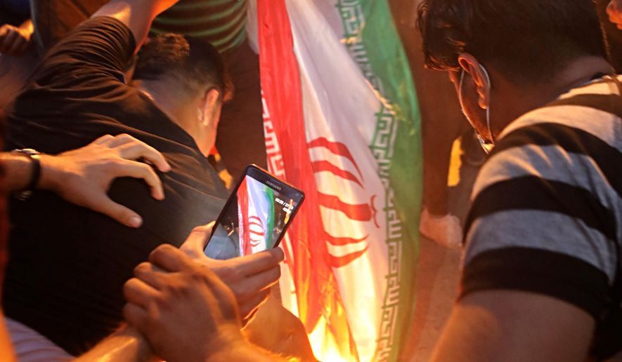 In this Friday, Sept. 7, 2018 file photo, protesters burn an Iranian flag after storming and burning the Iranian consulate building in Basra, Iraq.  (AP Photo/Nabil al-Jurani, File) **FILE**