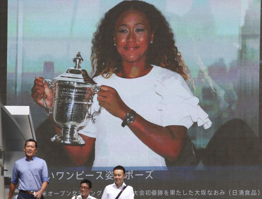 People walk by a huge screen showing US Open women's singles champion Naomi Osaka with her trophy, in Tokyo, Monday, Sept. 10, 2018. (AP Photo/Koji Sasahara)