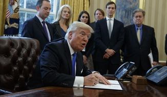 FILE - In this Jan. 24, 2017, file photo, President Donald Trump signs an executive order on the Keystone XL pipeline in the Oval Office of the White House in Washington. Native American tribes in Montana and South Dakota say the Trump administration unlawfully approved the Keystone XL oil pipeline without considering potential damage to cultural sites. Attorneys for the Fort Belknap and Rosebud Sioux tribes sued the U.S. State Department Monday, Sept. 10, 2018, asking a court to rescind the permit. (AP Photo/Evan Vucci, File)