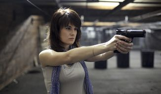 In this photo taken on Sunday, April 22, 2012, Maria Butina, a gun-rights activist poses for a photo at a shooting range in Moscow, Russia. When gun activist Maria Butina arrived in Washington in 2014 to network with the NRA, she was peddling a Russian gun rights movement that was already dead. Fellow gun enthusiasts and arms industry officials describe the strange trajectory of her Russian gun lobby project, which U.S. prosecutors say was a cover for a Russian influence campaign. Accused of working as a foreign agent, Butina faces a hearing Monday, Sept. 10 in Washington.(AP Photo/Pavel Ptitsin)