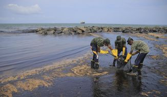 Sri Lankan army soldiers remove oil slick and sand from a beach following an oil spill in Uswetakeiyawa, a coastal town north of Colombo, Sri Lanka, Monday, Sept. 10, 2019. Sri Lanka deployed hundreds of coast guard and navy personnel on Monday to clean oil slicks on a coastal stretch near the capital following a spill caused by a pipeline leak. (AP Photo/Eranga Jayawardena) ** FILE **