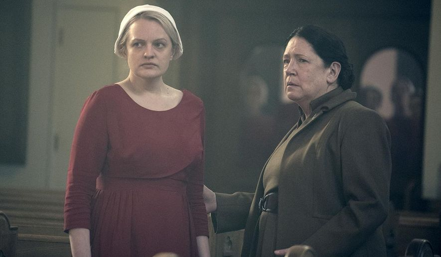 "This image released by Hulu shows Elisabeth Moss, left, and Ann Dowd in a scene from ""The Handmaid's Tale."" The program was nominated for an Emmy on Thursday for outstanding drama series. The 70th Emmy Awards will be held on Monday, Sept. 17. (George Kraychyk/Hulu via AP)"