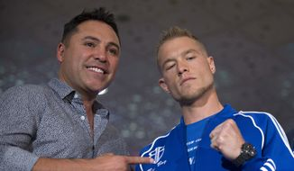 Boxing promoter Oscar De La Hoya, left, poses with junior middleweight boxer Brandon Cook of Canada at the MGM Grand hotel-casino in Las Vegas Tuesday, Sept. 11, 2018. Cook will challenge undefeated WBO junior middleweight champion Jaime Munguia of Mexico at T-Mobile Arena in Las Vegas on Sept. 15. (Steve Marcus/Las Vegas Sun via AP) **FILE**