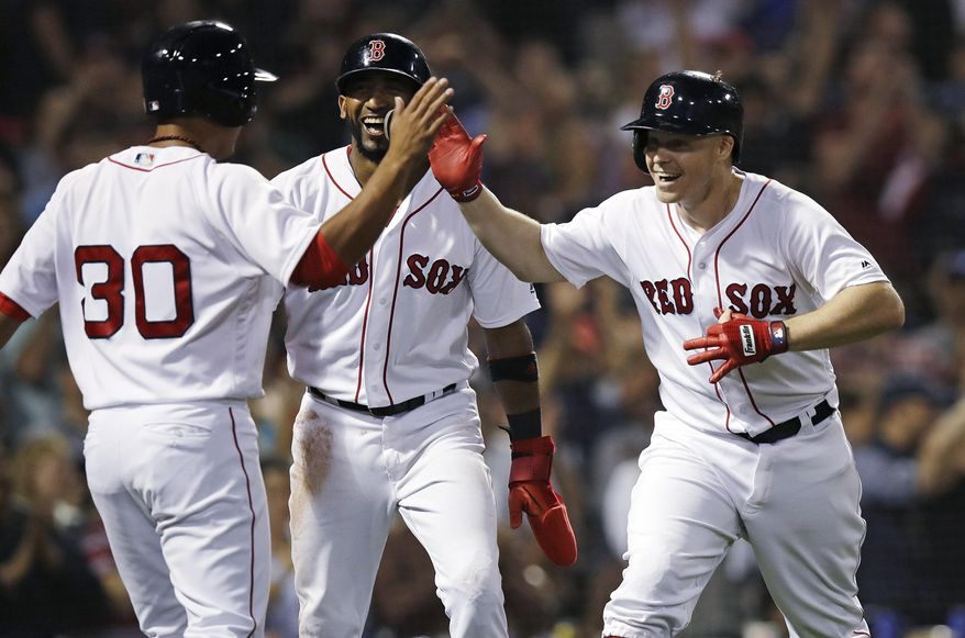 Boston Red Sox's Brock Holt, right, celebrates with Tzu-Wei Lin (30) and Eduardo Nunez, center, after his pinch-hit, three-run home run off Toronto Blue Jays relief pitcher Ryan Tepera during the seventh inning of a baseball game at Fenway Park in Boston, Tuesday, Sept. 11, 2018. (AP Photo/Charles Krupa)
