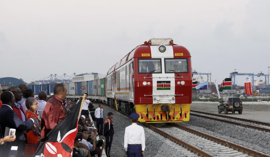 FILE - In this May 30, 2017, file photo, Kenyan President Uhuru Kenyatta, 3rd left, watches during the opening of the SGR cargo train runs on a China-backed railway from the port containers depot in Mombasa Kenya, to Nairobi. A wave of Chinese-financed railways and other trade links in Africa and Asia that have prompted worries about debt and Beijing's ambitions is reducing politically dangerous inequality between regions within countries, a multinational group of researchers said Tuesday, Sept. 11, 2018. (AP Photo/Khalil Senosi, File) **FILE**