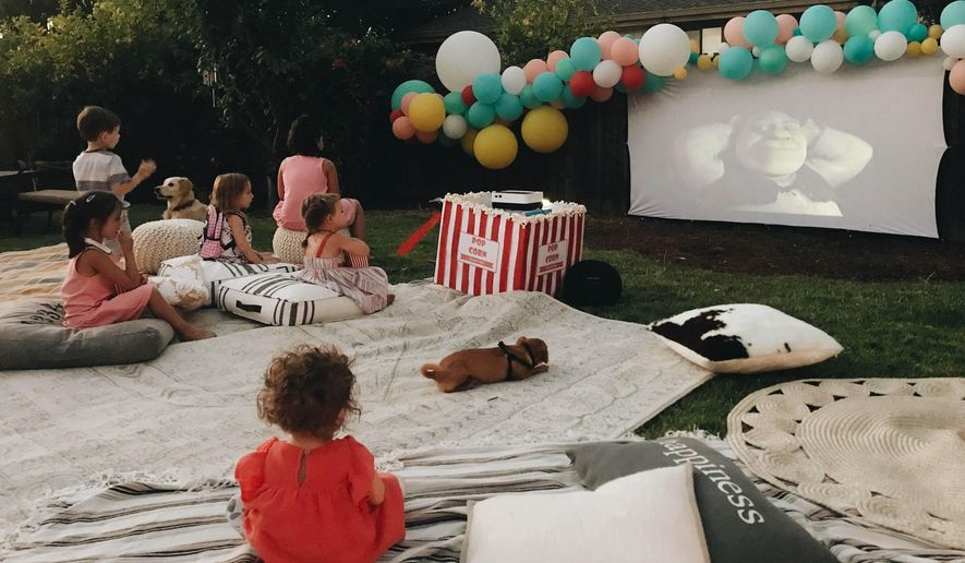 "This photo provided by Wittybash.com shows children at a backyard birthday party watching the movie ""Shrek"" on an outdoor theater setup in Concord, Calif. (Rozalyn Schlumpf/Wittybash.com via AP)"