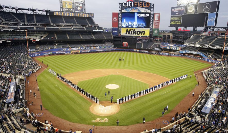 The Miami Marlins and the New York Mets joins members of the New York police and fire departments on the field for pregame ceremonies before a baseball game Tuesday, Sept. 11, 2018, in New York. (AP Photo/Frank Franklin II)