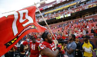 FILE - In this Sept. 1, 2018, file photo, Maryland offensive lineman Ellis McKennie waves a flag in remembrance of offensive lineman Jordan McNair, who died after collapsing on a practice field during a spring practice, after an NCAA college football game against Texas, in Landover, Md. Making the best of a bad situation, Maryland is unbeaten after two games and garnering votes in the Top 25 poll while playing for fallen teammate Jordan McNair and without head coach DJ Durkin. (AP Photo/Patrick Semansky, File) **FILE**
