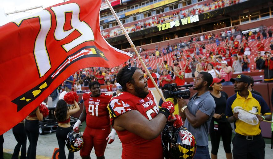 In this Sept. 1, 2018, file photo, Maryland offensive lineman Ellis McKennie waves a flag in remembrance of offensive lineman Jordan McNair, who died after collapsing on a practice field during a spring practice, after an NCAA college football game against Texas, in Landover, Md. Making the best of a bad situation, Maryland is unbeaten after two games and garnering votes in the Top 25 poll while playing for fallen teammate Jordan McNair and without head coach DJ Durkin. (AP Photo/Patrick Semansky, File) **FILE**