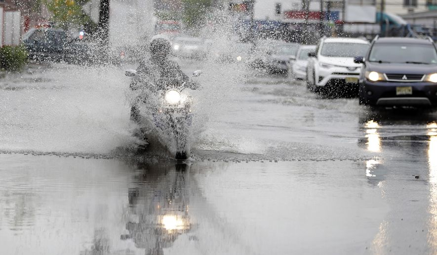 FILE- In this May 5, 2017, file photo, Ramadan Abdelaziz, of Jersey City, N.J., rides his motorcycle over floodwaters on his way home from work in Newark, N.J. A federal safety agency is recommending that all new motorcycles built for road use in the U.S. have anti-lock brakes and electronic stability control as standard equipment. Antilock brakes have been required in U.S. passenger cars since 2000. They pump the brakes many times per second to stop wheels from locking up and skidding. Electronic stability control applies brakes and power to the wheels to keep a vehicle stable. (AP Photo/Julio Cortez, File)