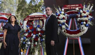 Paris Mayor Anne Hidalgo and Los Angeles Mayor Eric Garcetti pose with wreaths during a ceremony marking the 17th anniversary of the Sept. 11, 2001 terrorist attacks on the United States, at the Los Angeles Fire Department's training center Tuesday, Sept. 11, 2018. In the right background is the largest fragment of the World Trade Center outside New York.   (AP Photo/Reed Saxon)