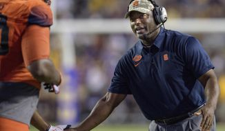 FILE - In this Sept. 23, 2017, file photo, Syracuse coach Dino Babers celebrates a touchdown with his team against LSU in the second half of an NCAA college football game in Baton Rouge, La. Syracuse has won its first two games for the first time under Babers, in his third season with the Orange, and his uptempo offense is purring. (AP Photo/Matthew Hinton, File)