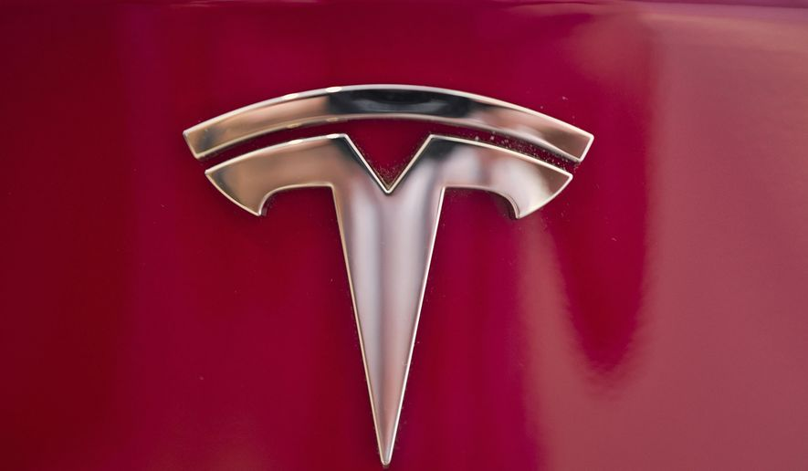 """FILE - This Aug. 8, 2018, file photo shows a Tesla emblem on the back end of a Model S in the Tesla showroom in Santa Monica, Calif. Tesla is dropping two of the seven standard colors it had offered to customers to streamline production. In a tweet early Tuesday, Sept. 11, CEO Elon Musk said obsidian black and metallic silver will still be available, but at a higher cost. Tesla fans can still get solid black and """"midnight silver metallic,"""" as well as pearl white, deep blue metallic and red as standard color choices. (AP Photo/Richard Vogel, File)"""