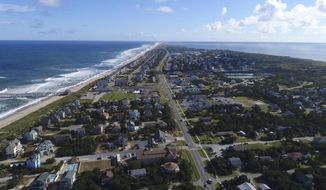 """In this Monday afternoon, Sept. 10, 2018 photo provided by DroneBase, waves crash along Avon, N.C., in the Outer Banks ahead of Hurricane Florence. Hurricane Florence churned Tuesday, Sept. 11, toward the Eastern Seaboard as a storm of """"staggering"""" size, forcing a million people to evacuate the coast. (DroneBase via AP)"""