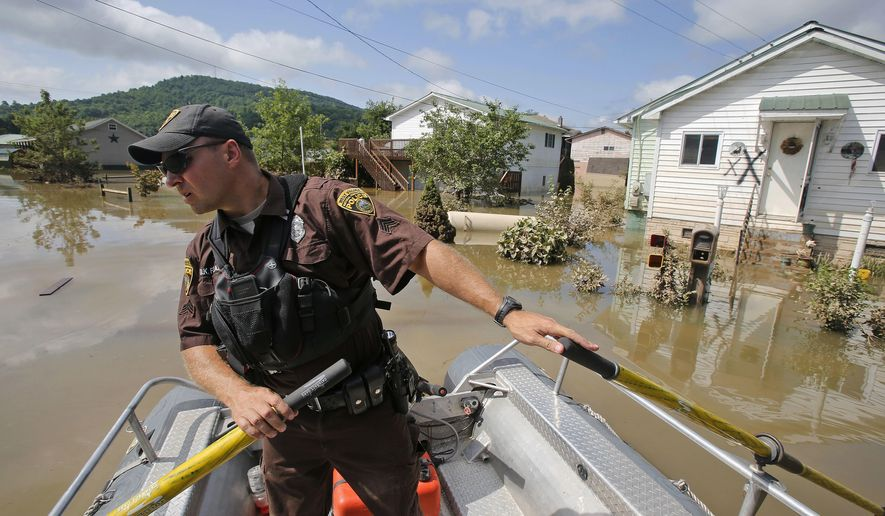 "FILE - In this Saturday, June 25, 2016 file photo, Lt. Dennis Feazell, of the West Virginia Department of Natural Resources, watches for debris as he and a co-worker search flooded homes in Rainelle, W. Va. National Weather Service guidance says the currently projected scenario from Hurricane Florence ""could result in catastrophic flooding rainfall"" across the mountains of western North Carolina, western Virginia, and eastern West Virginia late this week.(AP Photo/Steve Helber, File)"