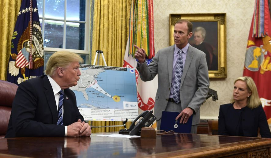 President Donald Trump, left, listens as FEMA Administrator Brock Long, center, talks about Hurricane Florence in the Oval Office of the White House in Washington, Tuesday, Sept. 11, 2018. Homeland Security Secretary Kirstjen Nielsen listens at right. (AP Photo/Susan Walsh)