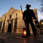 Dan Phillips, a member of the San Antonio Living History Association, collects lanterns following a pre-dawn memorial ceremony to remember the 1836 Battle of the Alamo and those who fell on both sides, Wednesday, March 6, 2013, in San Antonio. (AP Photo/Eric Gay)