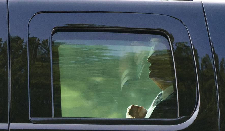 President Donald Trump is seen through the window of his motorcade vehicle as he is driven to board Martine One at Walter Reed National Military Medical Center in Bethesda, Md., Tuesday, May 15, 2018, en route to Washington. The White House says first lady Melania Trump is hospitalized after undergoing a procedure to treat a benign kidney condition. (AP Photo/Carolyn Kaster)