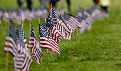 Staff and day program participants from Pittsburgh Mercy Intellectual Disabilities Services place flags on the graves of veterans at the Allegheny Cemetery in Pittsburgh, Wednesday, May 23, 2018, for the upcoming Memorial Day holiday weekend. (AP Photo/Keith Srakocic)