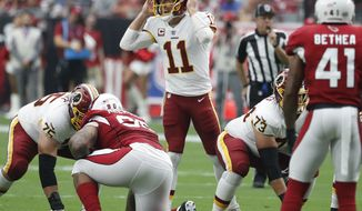 "FILE - In this Sept. 9, 2018, file photo, Washington Redskins quarterback Alex Smith (11) makes a call during the first half of an NFL football game against the Arizona Cardinals, in Glendale, Ariz. A franchise known for the ""Hogs"" offensive line from the Super Bowl era, the Washington Redskins might have another season-altering group in the trenches this season. Washington's ""Hogs 2.0"" offensive line is a dream to play behind for running back Adrian Peterson and quarterback Alex Smith.(AP Photo/Rick Scuteri, File)"