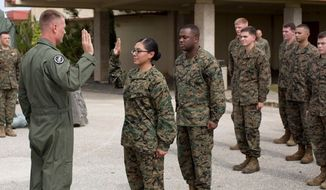 Cpl. Remedios Cruz, Marine Aircraft Group 12, seen here during an enlistment ceremony in December 2013, will exit the military after pleading guilty to maintaining a romantic relationship with a subordinate.(Image: U.S. Marine Corps, Lance Cpl. Richard Currier) ** FILE **