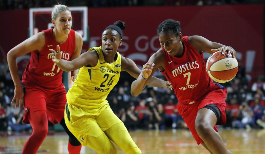 Washington Mystics guard Ariel Atkins (7) drives to the basket as teammate Washington Mystics forward Elena Delle Donne (11) is left and Seattle Storm guard Jewell Loyd (24) defends during the first half of Game 3 of the WNBA basketball finals, Wednesday, Sept. 18 2018, in Fairfax, Va. (AP Photo/Carolyn Kaster)