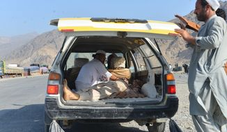 Men carry a dead body with a civilian vehicle in Momandara district of Nangarhar province, Afghanistan, Tuesday, Sept. 11, 2018. A suicide bomber detonated his explosives-filled vest among a group of people protesting a local police commander in eastern Afghanistan on Tuesday, killing 25 and wounding about 130, a provincial official said. (AP Photo/Mohammad Anwar Danishyar)