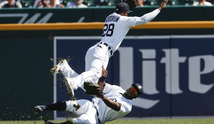Detroit Tigers left fielder Christin Stewart, bottom, makes the catch on a Houston Astros' Evan Gattis fly ball as shortstop Niko Goodrum (28) collides with him in the second inning of a baseball game in Detroit, Wednesday, Sept. 12, 2018. (AP Photo/Paul Sancya)
