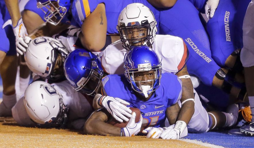Boise State wide receiver Akilian Butler (81) looks up from under the pile of players he dragged in to the end zone for a touchdown against Connecticut in the second half of an NCAA college football game, Saturday, Sept. 8, 2018, in Boise, Idaho. Boise State won 62-7. (AP Photo/Steve Conner)
